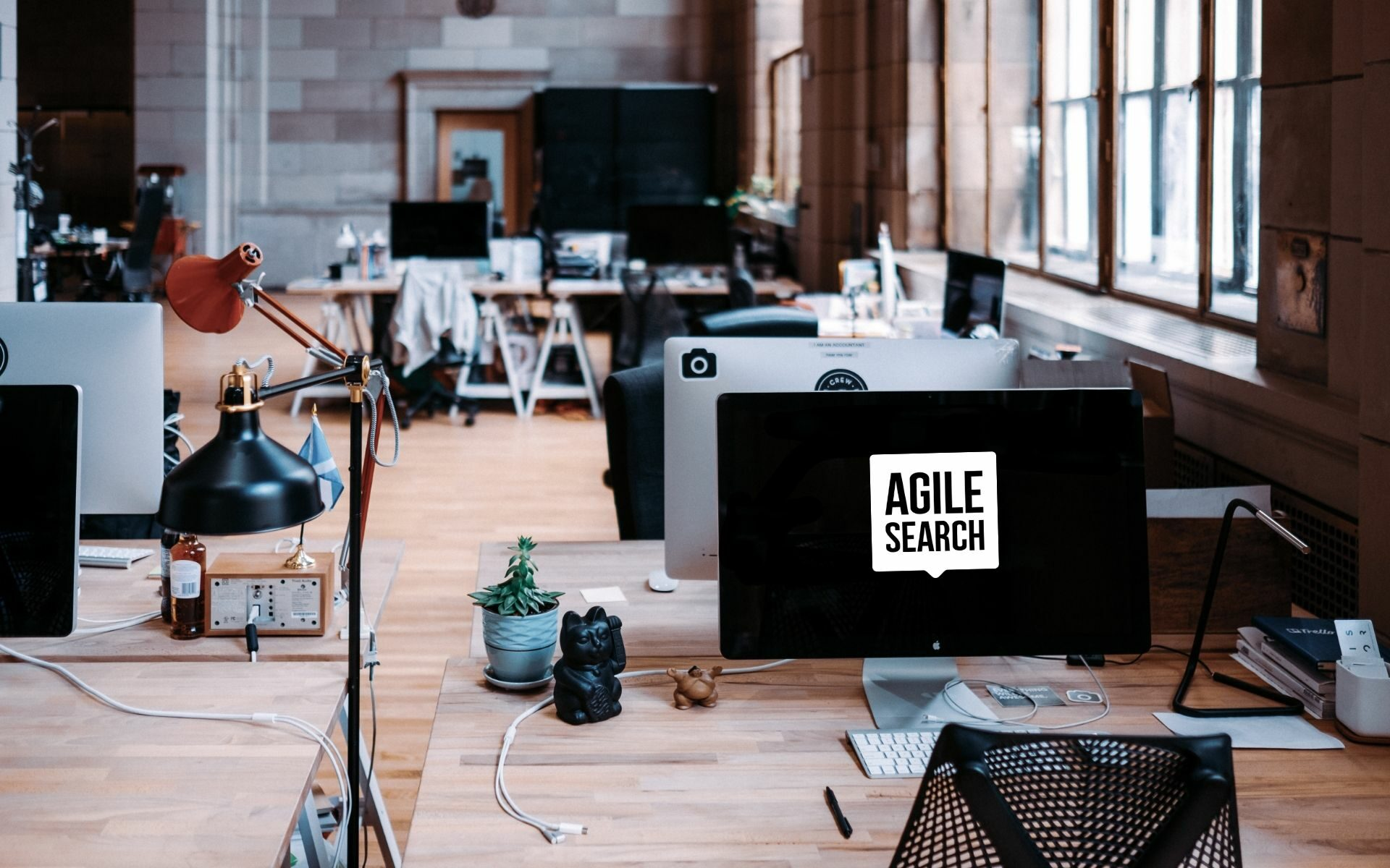 Computer screen with tech recruitment company Agile Search logo on a desk in an empty office.
